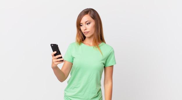 Mooie vrouw die zich verdrietig, overstuur of boos voelt en opzij kijkt en een smartphone gebruikt