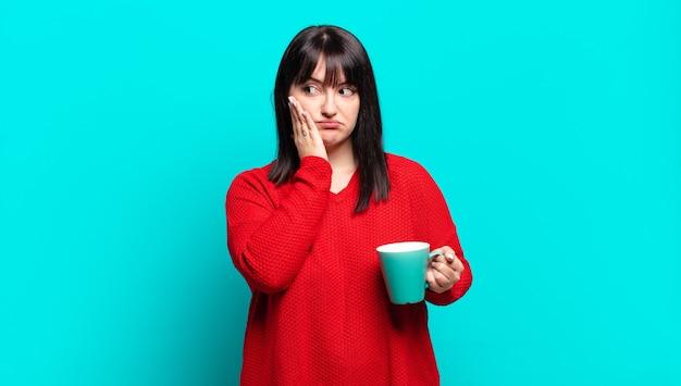 Mooie vrouw die zich verveeld, gefrustreerd en slaperig voelt na een vermoeiende, saaie en vervelende taak, gezicht met hand vasthoudend