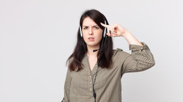 Mooie vrouw die zich verward en verbaasd voelt en laat zien dat je gek bent. assistent-agent met een headset