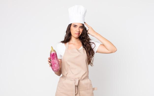 Mooie vrouw die zich verward en verbaasd voelt en laat zien dat je gek bent met een schort en een aubergine in de hand
