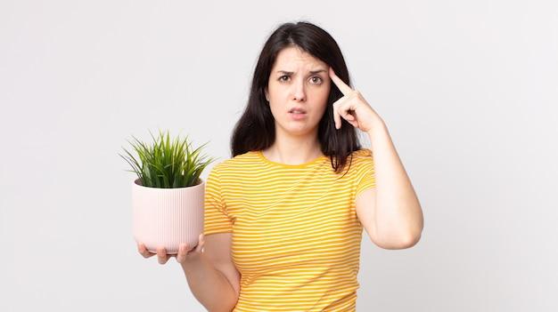 Mooie vrouw die zich verward en verbaasd voelt, laat zien dat je gek bent en een decoratieve plant vasthoudt