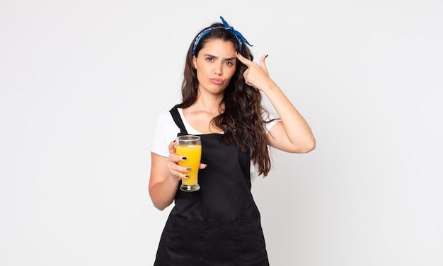Mooie vrouw die zich verward en verbaasd voelt, laat zien dat je gek bent en een glas sinaasappelsap vasthoudt