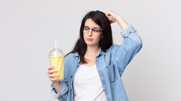 Mooie vrouw die zich verward en verward voelt, haar hoofd krabt en een vanillemilkshake vasthoudt