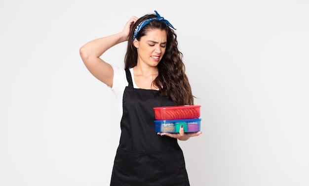 Mooie vrouw die zich verward en verward voelt, haar hoofd krabt en tupperwares met eten vasthoudt