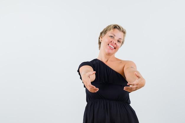 Mooie vrouw die zich voordeed als geschenkdoos in zwarte blouse te houden en op zoek blij Gratis Foto