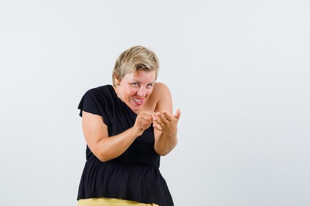 Mooie vrouw die zich voordeed als het schrijven van bericht op telefoon in zwarte blouse en op zoek verraderlijk.