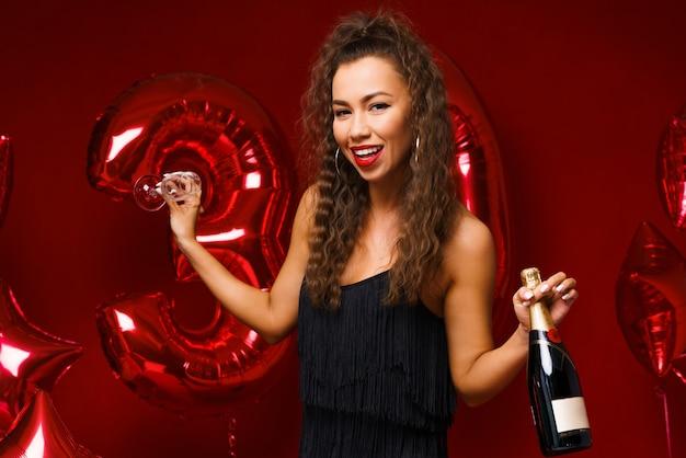 Mooie vrouw die zich voordeed op een rode achtergrond met ballonnen met een fles champagne in haar hand c...