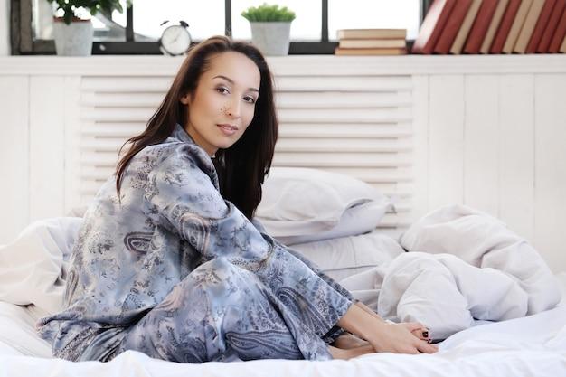Mooie vrouw die zich voordeed op het bed