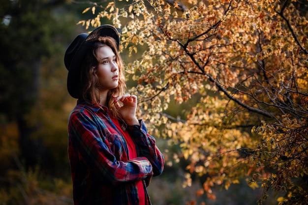 Mooie vrouw die zich voordeed op het bos in de herfst