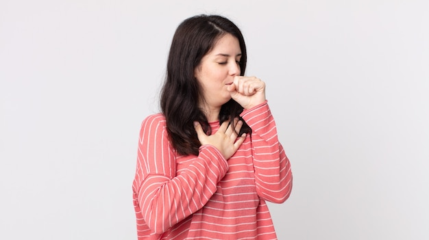 Mooie vrouw die zich ziek voelt met keelpijn en griepsymptomen, hoest met bedekte mond
