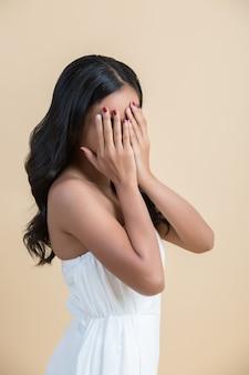 Mooie vrouw die zijn gezicht verbergt