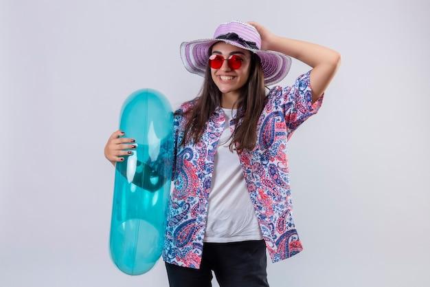 Mooie vrouw die zomerhoed en rode zonnebril draagt die opblaasbare ring positief houdt en gelukkig lachend vrolijk haar hoed staande te raken