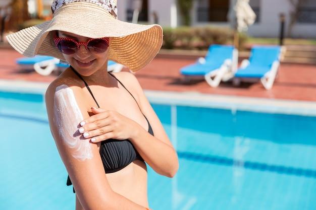 Mooie vrouw die zonnebrandcrème aanbrengt met haar handen op een gebruinde schouder bij het zwembad