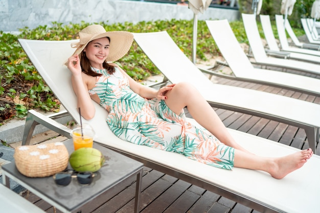 Mooie vrouw die zonnebril en een overzeese hoed draagt, die zij jus d'orange drinkt en zij zit
