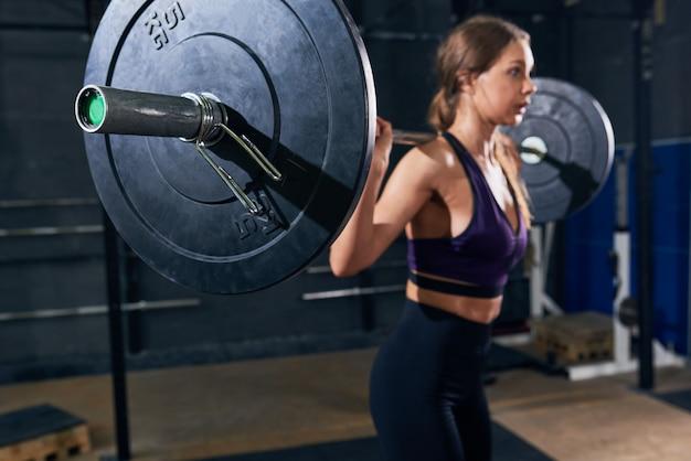 Mooie vrouw die zware barbell in gymnastiek houden