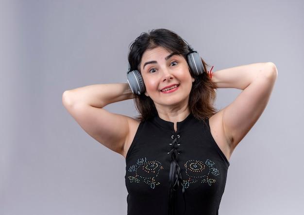 Mooie vrouw die zwarte blouse draagt die aan muziek via hoofdtelefoons luistert