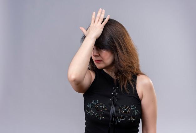 Mooie vrouw die zwarte blouse draagt die boos en beu met iets kijkt