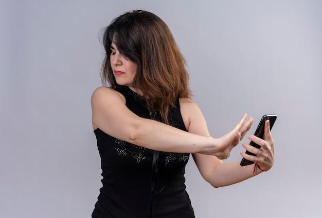 Mooie vrouw die zwarte blouse draagt die boos weigert om iets op de telefoon over grijze achtergrond te bekijken