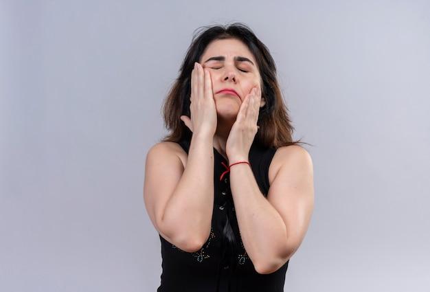 Mooie vrouw die zwarte blouse draagt die haar gezicht met handen masseert