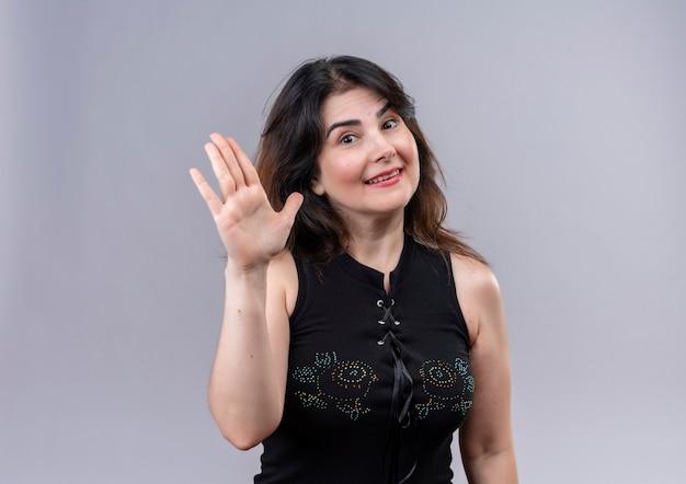 Mooie vrouw die zwarte blouse draagt die hallo zegt