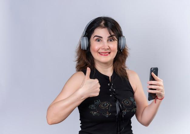 Mooie vrouw die zwarte blouse draagt die het doen gelukkige duimen omhoog in hoofdtelefoons met telefoon kijkt