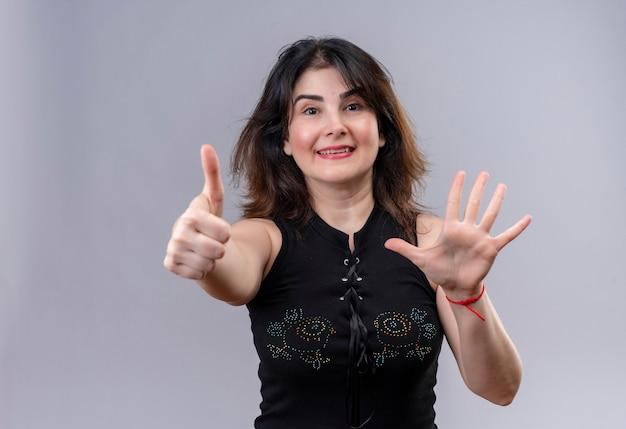 Mooie vrouw die zwarte blouse draagt die het doen gelukkige duimen omhoog kijkt en vijf teken toont