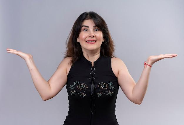 Mooie vrouw die zwarte blouse draagt die het is eenvoudig teken toont dat haar wapens opent