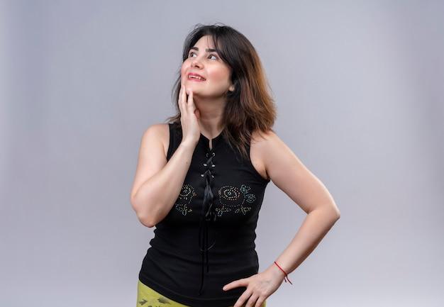 Mooie vrouw die zwarte blouse draagt die in gedachten omhoog kijkt