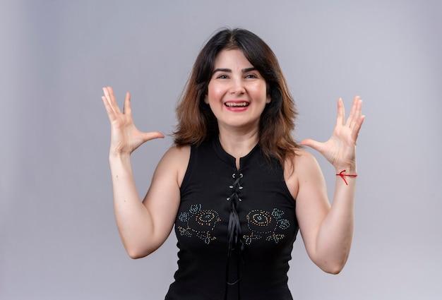 Mooie vrouw die zwarte blouse draagt die vreugdevol grootte met handen toont