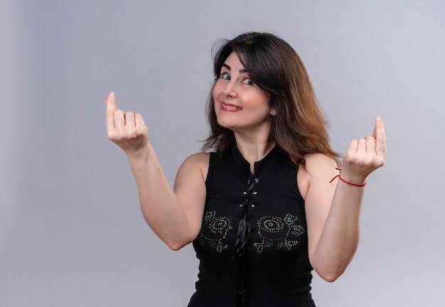 Mooie vrouw die zwarte blouse draagt die zich over geld afvraagt dat geldteken met vingers toont