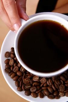 Mooie vrouw die zwarte koffie drinkt