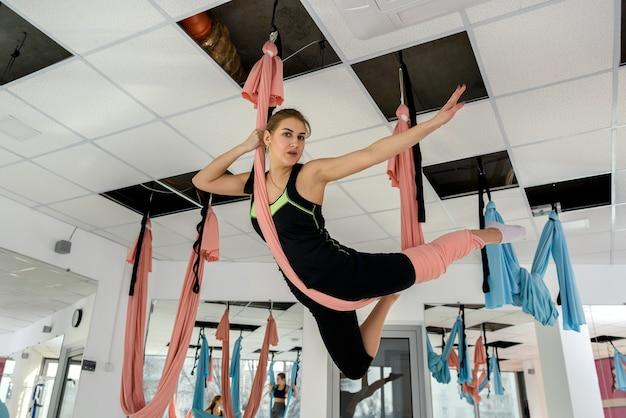 Mooie vrouw doet aerial yoga oefeningen in de klas