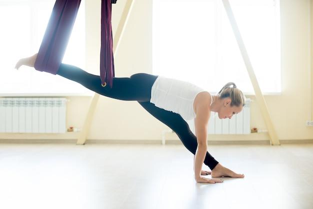 Mooie vrouw doet hanumanasana yoga in hangmat