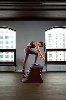 Mooie vrouw doet pilates oefening, training op vaten. fitnessconcept, speciale fitnessapparatuur, gezonde levensstijl, plastic. kopieer ruimte, sportbanner voor reclame.