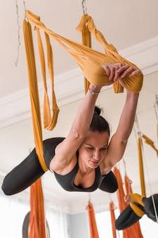 Mooie vrouw doet vliegyoga op hangmatten die de rugtraining in gymnastiek uitrekken