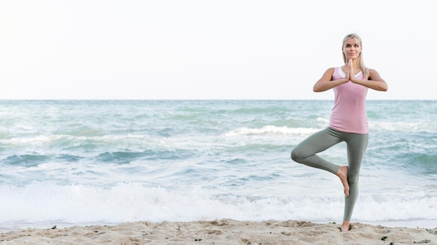 Mooie vrouw doet yoga op het strand