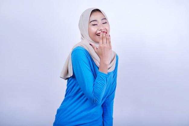 Mooie vrouw draagt blauw t-shirt en hijab lachend haar ogen sluiten