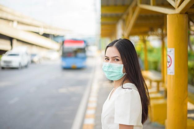 Mooie vrouw draagt gezichtsmasker in bushalte