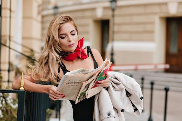 Mooie vrouw draagt gouden hanger krant lezen tijdens het wachten vriend op straat