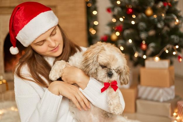 Mooie vrouw draagt kerstmuts en witte trui, houdt haar hond vast, veel plezier samen, wintervakantie thuis doorbrengen in de buurt van versierde groene kerstboom en open haard in de woonkamer.