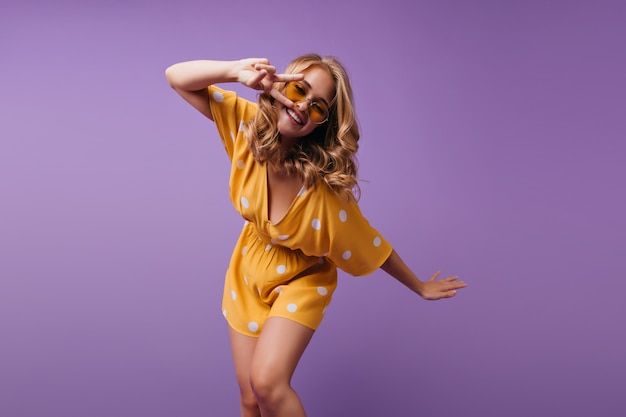 Mooie vrouw draagt oranje jurk en gele zonnebril dansen met vrolijke glimlach. indoor portret van spectaculair meisje met golvend haar plezier.