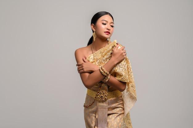 Mooie vrouw draagt thaise kleding en staat om haar borsten te knuffelen.