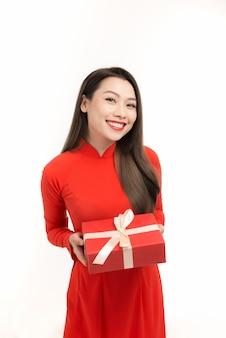 Mooie vrouw draagt vietnamese traditionele kleding, houdt nieuwjaarsgeschenkdoos aanwezig, geïsoleerd op wit