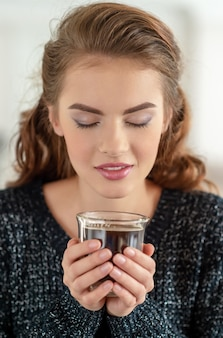 Mooie vrouw drinkt koffie en geniet van de smaak. vrij jong volwassen meisje ontspannen met een kopje thee.