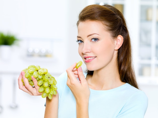 Mooie vrouw druiven eten is op de keuken