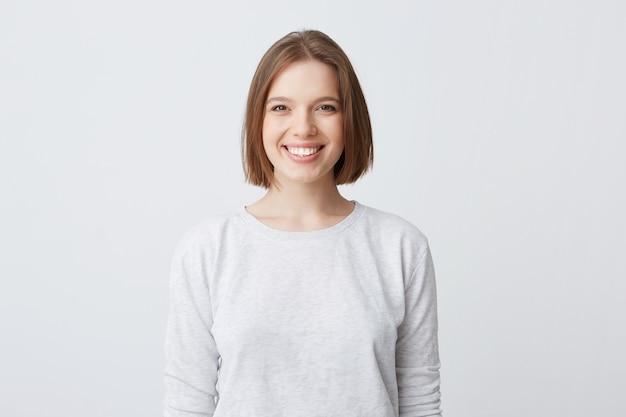 Mooie vrouw drukt gelukkige emoties uit, heeft een brede, aangename glimlach, draagt een witte longsleeve en voelt zich tevreden