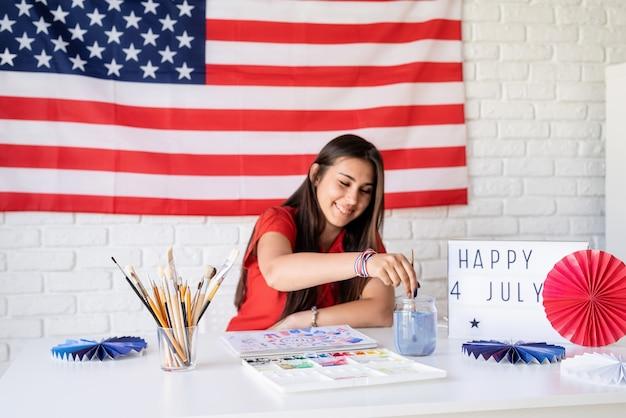 Mooie vrouw een aquarel illustratie tekenen voor de dag van de onafhankelijkheid van de vs selectieve focus focus op voorgrond happy 4 juli de tekst op de lightbox