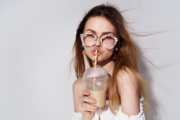 Mooie vrouw een glas met een drankje in de hand mode lichte achtergrond. hoge kwaliteit foto