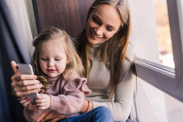 Mooie vrouw en haar schattige dochtertje doen selfie met behulp van een slimme telefoon