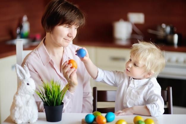 Mooie vrouw en haar schattige zoon of kleinzoon spelen met easter egg op paasdag